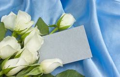 White roses blank gift tag celebration. Blank silver gift tag or card on blue silk with a bouquet of white roses royalty free stock photos