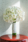 White roses bouquet. Decorated with crystals and put on striped red chair. Selective focus Stock Photography