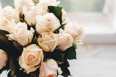 White roses bouquet on wooden background in light, space for tex Royalty Free Stock Photos