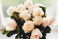 White roses bouquet on wooden background in light, space for tex Stock Photos