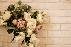 White roses are with brick wall background. Stock Photography