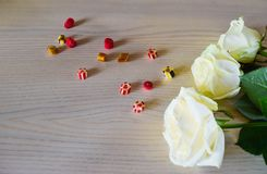 White roses and candies. royalty free stock photography