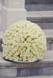 White roses centerpiece flower ball. White rose flower ball, a large outdoor festive centerpiece standing on the stairs with a white fence in the background. A royalty free stock photos