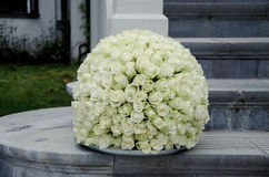 White roses centerpiece flower ball. White rose flower ball, a large outdoor festive centerpiece standing on the stairs with a white fence in the background. A stock image