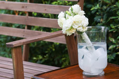 White roses in a glass vase. And a wood bench Royalty Free Stock Photos