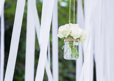 White roses in a glass vase with white ribbons. In background Stock Photography