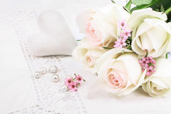 White roses and heart on tablecloth Stock Image