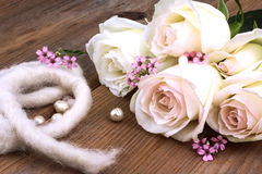 White roses and perls, festivity. White roses on old wooden table Royalty Free Stock Photo