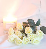 White Roses. This photo shows some White Roses displayed by a burning scented candle stock image