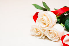 White roses with red ribbon on a light wooden background. Women' Stock Photos