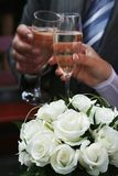 White roses and two hands holding goblets. Stock Photo