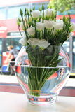 White roses in vase with London bus background Stock Photography