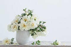 White roses in vase. On wooden table stock photography