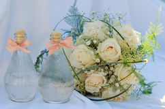 White roses wedding bouquet with a bottles. White roses wedding bouquet at the white background with two bottles Royalty Free Stock Photos