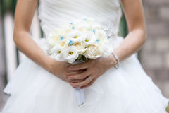 White roses wedding bouquet in bride`s hand. White roses and lisianthus wedding bouquet in bride`s hand Royalty Free Stock Photo
