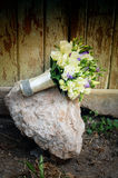 White roses wedding bouquet. At stone and in front of old wooden door Stock Photo