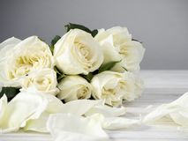 White roses on a white wooden table stock image