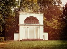 White rotunda in the park. Classical white rotunda with white columns in the park, photo filter Royalty Free Stock Photography
