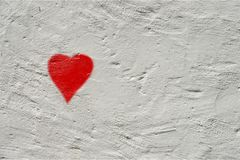 White rough wall with a small red painted heart Royalty Free Stock Photo