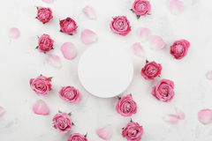White round blank, pink rose flowers and petals for spa or wedding mockup on light background top view. Beautiful floral pattern. stock photo
