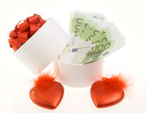 White round box with banknotes. And two red hearts Stock Photos