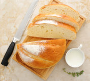 White round bread cut into slices with a mug of milk royalty free stock image