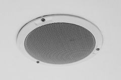 White round circle speaker and grille hanging on ceiling. White round circle speaker and grille hanging on white ceiling. Selective focus royalty free stock photos