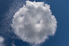 White round cloud, shaped like bun, on blue sky. Stock Images