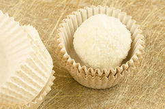 White, round, coconut chocolate sweats and paper packaging  on golden background Royalty Free Stock Image