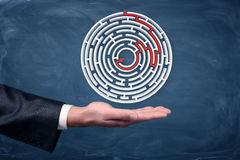 A white round maze with a way to the center drawn by a red arrow hovering over businessman`s palm. Best solution. Walkthrough. Avoid trouble Stock Images