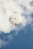 White round parachute on background blue sky with clouds. Royalty Free Stock Image
