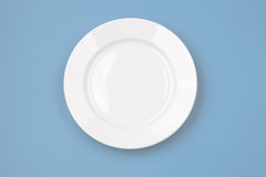 White round plate on blue background top view Royalty Free Stock Photos