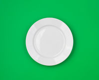 White round plate on green top view Stock Images