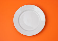 White round plate on orange top view Royalty Free Stock Image