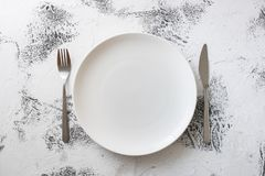 White Plate on white wooden background with utensils Royalty Free Stock Images