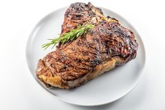 White round plate with Whole grilled T-bone steak and rosemary. Isolated on white background stock image