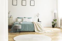 White round rug in front of green bed with blanket in bedroom in. Terior with posters. Real photo stock photos