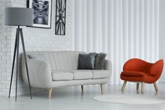 Orange modern living room. White round rug in front of orange armchair and settee in modern living room interior with grey lamp Royalty Free Stock Image