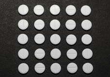 White round tablets in the shape of a square on a dark background Royalty Free Stock Photos