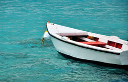 White row boat in clear blue water. White wooden row boat floating in the clear blue tropical waters of Bonaire Royalty Free Stock Photography