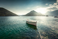 White rowboat moored at bay surrounded by mountains Stock Image