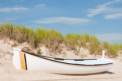 White Rowboat on Sandy Dune Stock Images