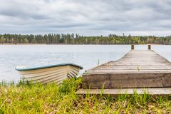 White Rowing Boat Next to Wooden Pier. With a Cloudy Grey and White Sky in the Background Stock Photo
