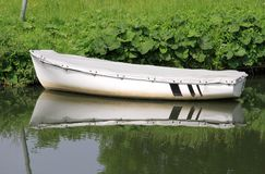 White rowing boat on the river bank Royalty Free Stock Images