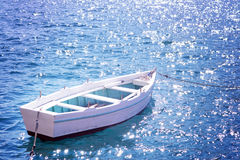 White rowing boat on the water with a spark of sea waves, summer Stock Images
