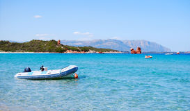 White rubber boat in the clear blue sea and mountains in the bac. Kground for tourism in sardinia stock photo