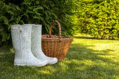White rubber boots and wicker basket stand on green glade in sunny summer forest. Stock Photography