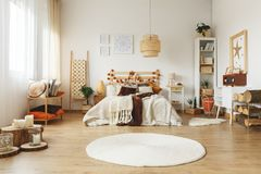 White rug in bedroom. Round white rug on the floor in bright bedroom Stock Photo