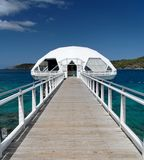 White Runway. White bridge and cottage in blue caribbean water Stock Images