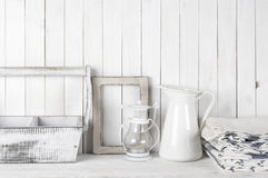 White rustic still life. Rustic still life in white color: shabby wood box and photo frame, jug, lantern and towels against white wood wall Royalty Free Stock Images